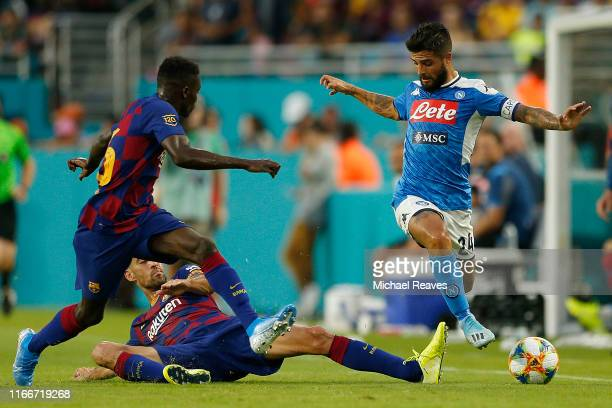 Lorenzo Insigne of SSC Napoli leaps over Sergio Busquets of FC Barcelona during a preseason friendly match at Hard Rock Stadium on August 07 2019 in...