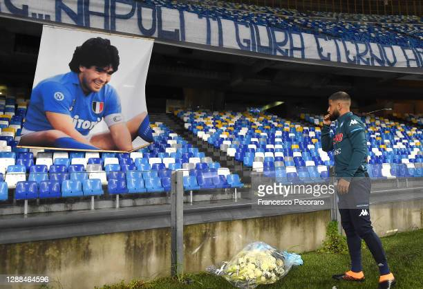 Lorenzo Insigne of S.S.C. Napoli places tributes next to a banner showing an images of the deceased Diego Maradona during the Serie A match between...