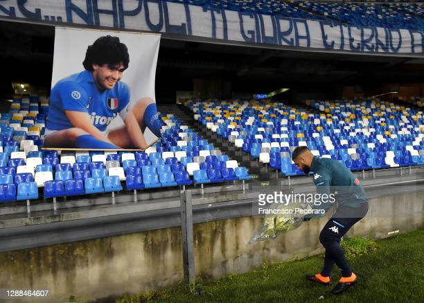 Lorenzo Insigne of S.S.C. Napoli places tributes next to a banner showing an images of the deceased Diego Maradona prior to the Serie A match between...