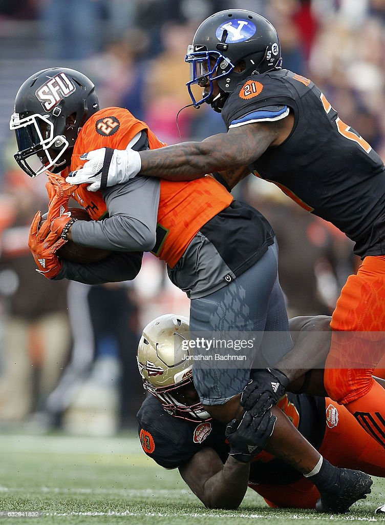 Lorenzo Jerome #22 of the North team is tackled by Jamaal Williams #21 of the South team and Freddie Stevenson #43 of the South team during the second half of the Reese's Senior Bowl at the Ladd-Peebles Stadium on January 28, 2017 in Mobile, Alabama.