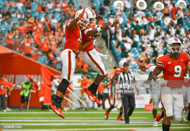 Lorenzo Lingard and Lawrence Cager of the Miami Hurricanes celebrate a touchdown in the third quarter against the Florida International Golden...