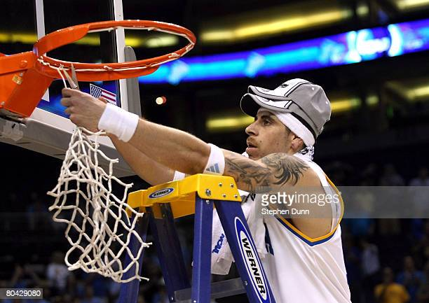 Lorenzo Mata-Rael of the UCLA Bruins cuts the net after his team defeated the Xavier Musketeers with the score of 76-57 to win the West Regional...