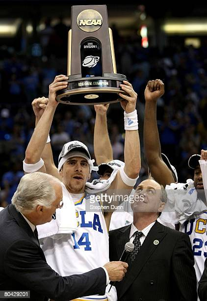 Lorenzo Mata-Rael of the UCLA Bruins hoists the West Regional trophy next to his coach Ben Howland following their victory over the Xavier Musketeers...