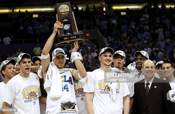 Lorenzo Mata-Rael of the UCLA Bruins hoists the West Regional trophy next to his coach Ben Howland and teammate Kevin Love following their victory...