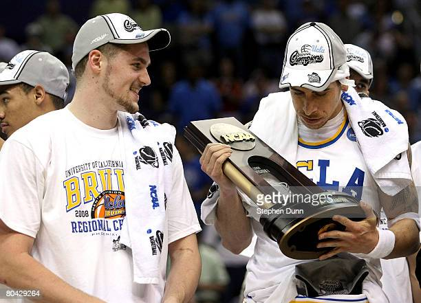 Lorenzo Mata-Rael of the UCLA Bruins holds the West Regional trophy next to teammate Kevin Love following their victory over the Xavier Musketeers in...