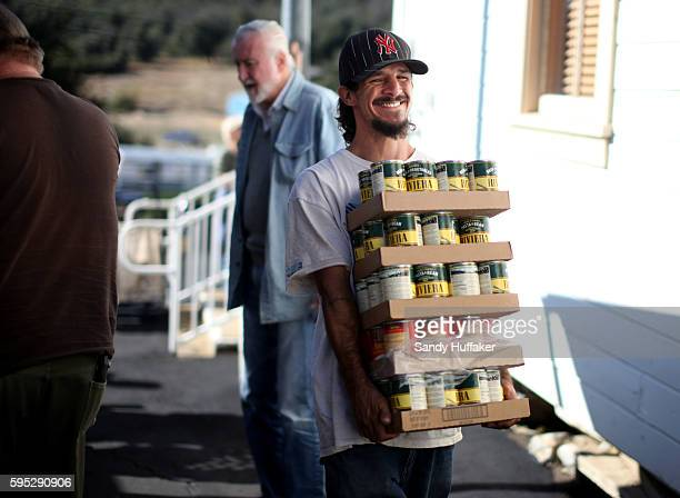Lorenzo Melentez carries food items from a Feeding America truck on Thursday November 3 2011 in Descanso California Feeding America is a charity...