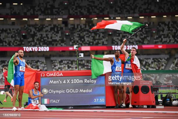 Lorenzo Patta, Lamont Marcell Jacobs, Eseosa Fostine Desalu and Filippo Tortu of Team Italy celebrate winning the gold medal in the Men's 4 x 100m...