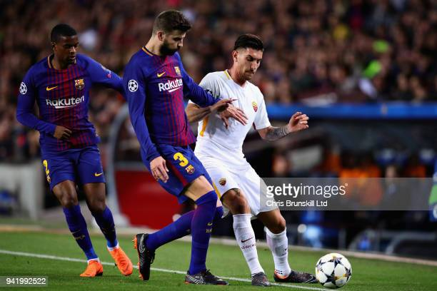 Lorenzo Pellegrini of AS Roma is challenged by Gerard Pique of FC Barcelona during the UEFA Champions League Quarter Final first leg match between FC...