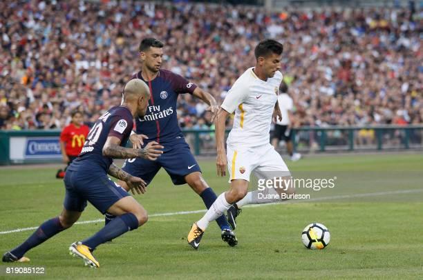 Lorenzo Pellegrini of AS Roma tries to maintain control off the ball against Layvin Kurzawa of Paris SaintGermain and Javier Pastore of Paris...