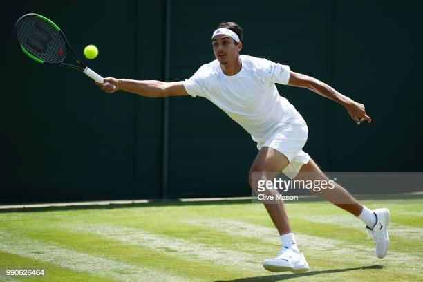 Lorenzo Sonego of Italy returns against Taylor Fritz of the United States during their Men's Singles first round match on day two of the Wimbledon...
