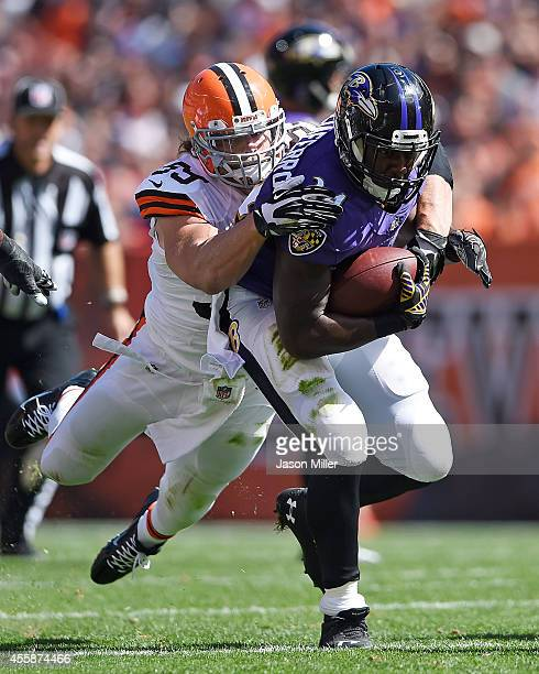 Lorenzo Taliaferro of the Baltimore Ravens gets dragged down by Tank Carder of the Cleveland Browns during the second quarter at FirstEnergy Stadium...