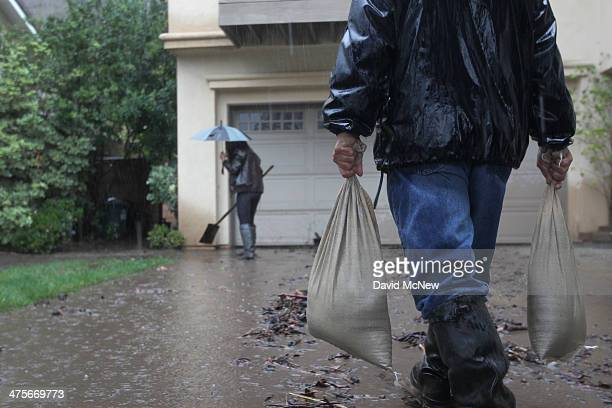 Lorenzo Tatone brings sandbags for this heighbor Mari Poblete to help control flooding at her home below the Colby Fire burn area as a storm brings...
