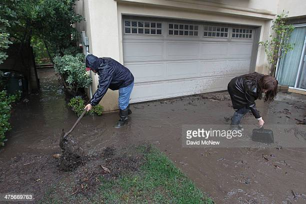 Lorenzo Tatone helps his neighbor Mari Poblete try to help control flooding at her home below the Colby Fire burn area as a storm brings rain in the...