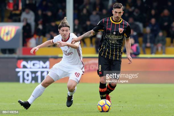 Lorenzo Venuti of Benevento competes for the ball with Riccardo Montolivo of Milan during the Serie A match between Benevento Calcio and AC Milan at...