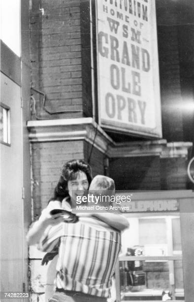Loretta Lynn hugs a man in joy while holding a record outside the Grand Ole Opry in circa 1960 in Nashville Tennessee