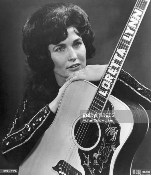 Loretta Lynn poses for a portrait holding a guitar that has her name spelled down the fretboard in circa 1961 in Nashville Tennessee