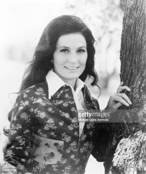 Loretta Lynn poses for a portrait leaning against a tree in circa 1975