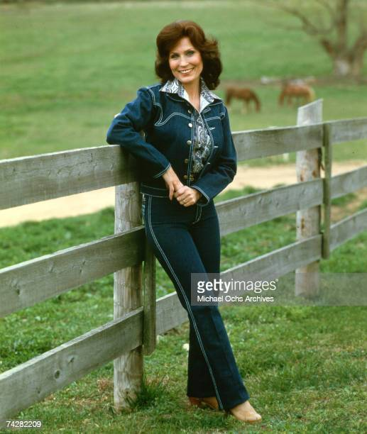 Loretta Lynn poses for a portrait wearing a blue denim suit with cows in the background leaning up against a fence in circa 1972