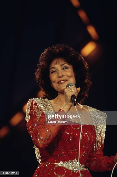 Loretta Lynn US country music singersongwriter singing into a microphone during a live concert performance at the International Festival of Country...