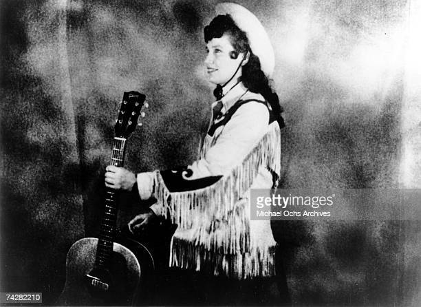 Loretta Lynn wears a cowboy hat and a fringe western style jacket while holding an acoustic guitar as she poses for a portrait in circa 1960 in...