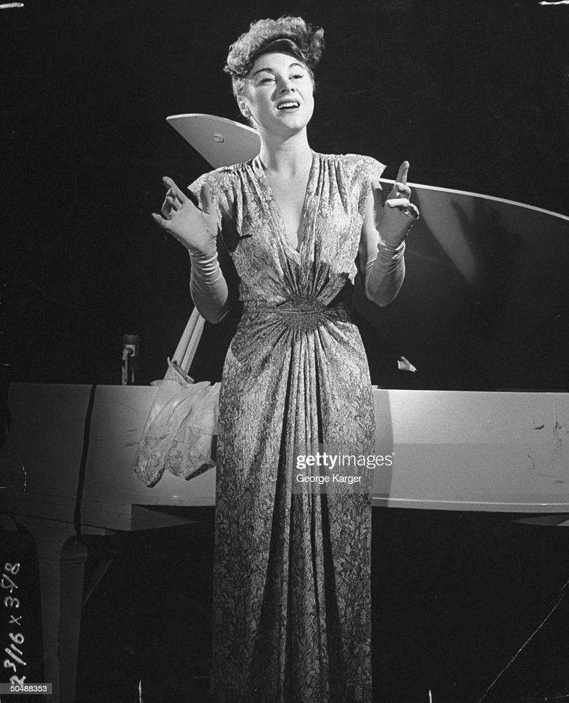 Loretta Sell Hildegarde singing at the piano.