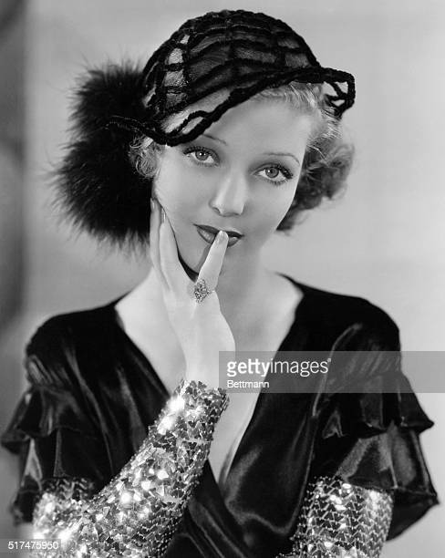 Loretta Young in a hat of chenille and net with two pom poms of black Marabou worn with black velvet dinner gown, tight sleeves of gold sequin...