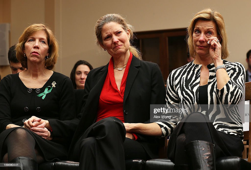 Lori Haas, whose daughter was shot and survived at the Virginia Tech shooting, Founder of ProtestEasyGuns.Com Abigail Spangler, and President of Million Mom March Martina Leinz hold hands as they listen to testimony of Superintendent of schools of Newtown, Connecticut, Janet Robinson about the shooting at Sandy Hook Elementary during a hearing before the House Democratic Steering and Policy Committee January 16, 2013 on Capitol Hill in Washington, DC. The committee held a hearing to focus on gun violence prevention.