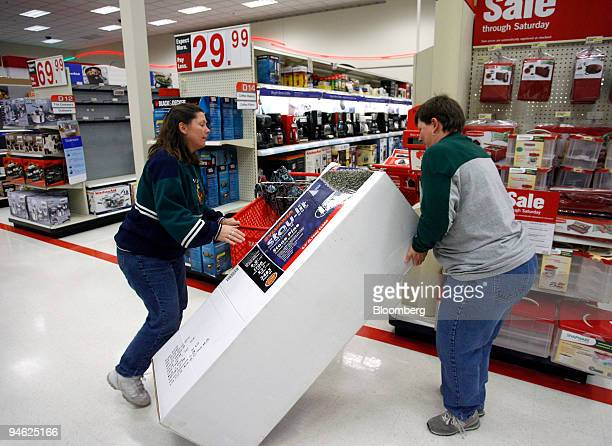 Lori Hanson left and Kim Hartman handle an artificial Christmas tree that has been reduced in price at a Target store in Mission Kansas US on...