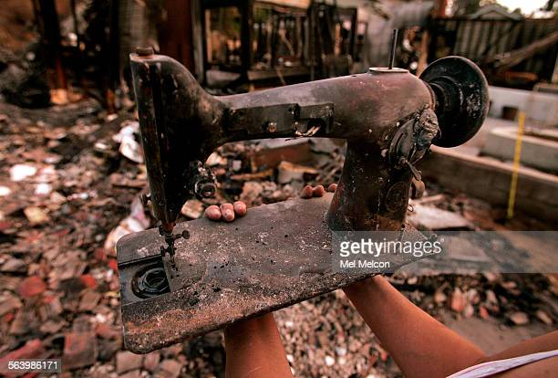 Lori Hutter holds up a Singer sewing machine from 1940 that was salvaged from a wildfire that destroyed her home on Valladares Dr in Rancho Bernardo...