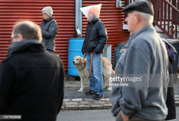 Lori Lobenstine wearing a dog cone and her dog Summitt participate in a group singalong safely distanced from each other in their Boston neighborhood...