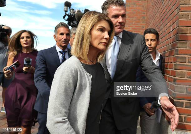 Lori Loughlin and her husband Mossimo Giannulli behind her at left leave the John Joseph Moakley United States Courthouse in Boston on Aug 27 2019 A...