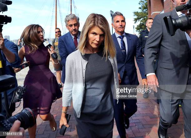 Lori Loughlin, center, and her husband Mossimo Giannulli, behind her at right, leave the John Joseph Moakley United States Courthouse in Boston on...