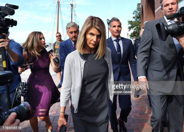 Lori Loughlin center and her husband Mossimo Giannulli behind her at right leave the John Joseph Moakley United States Courthouse in Boston on Aug 27...
