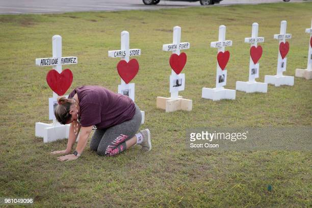Lori Simmons prays while visiting a memorial in front of Santa Fe High School on May 21 2018 in Santa Fe Texas Last Friday 17yearold student...