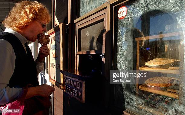 Lori Smith of Escondido chomps into a caramel apple at the Julian Cafe & Bakery sidewalk counter on Main Street in Julian, CA. Fresh apple pies fill...