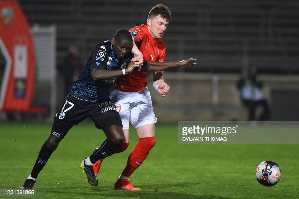 Lorient's French defender Houboulang Mendes challenges Nimes' Bosnian midfielder Haris Duljevic during the French L1 football match between Nimes...