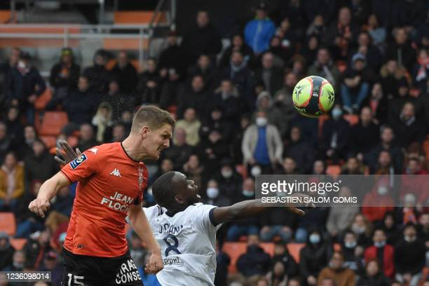 Lorient's French defender Julien Laporte heads the ball and scores his team's first goal during the French L1 football match between FC Lorient and...
