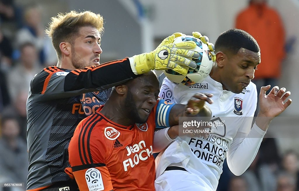 TOPSHOT - Lorient's French goalkeeper Benjamin Lecomte (L) grabs the ball during the French L1 football match between Lorient and Caen at Moustoir Stadium in Lorient on April 2, 2017. /