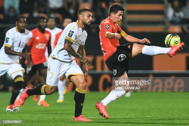 Lorient's French midfielder Laurent Abergel fights for the ball with Nice's French forward Andy Delort during the French L1 football match between...