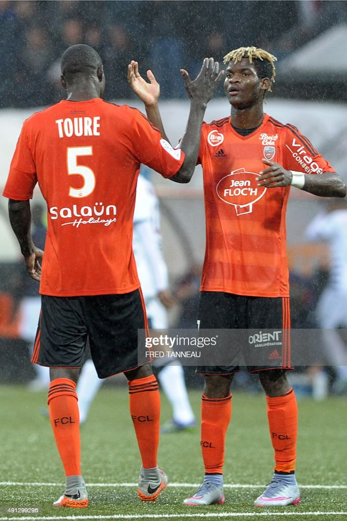 Lorient's midfielder Zargo Toure (L) celebrates with Lorient's forward Ibrahim Didier Ndong (R) during the French L1 football match between Lorient and Bordeaux at Moustoir Stadium in Lorient, western France, on October 4, 2015. Lorient won the match 3-2.