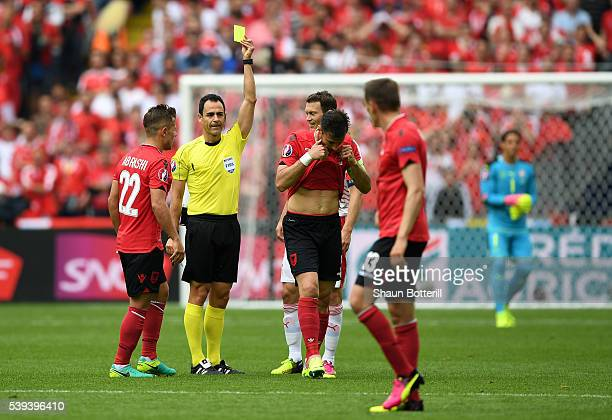 Lorik Cana of Albania is shown a yellow card by Referee Carlos Valesco Caballo during the UEFA EURO 2016 Group A match between Albania and...