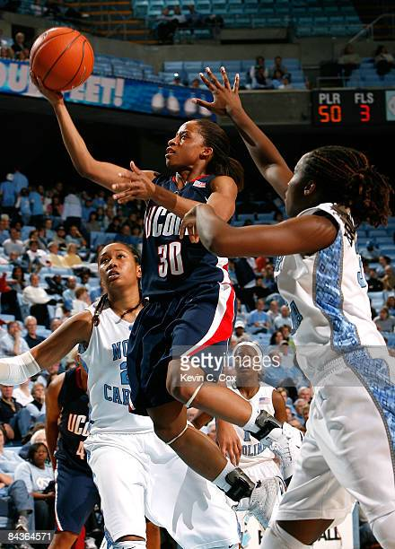 Lorin Dixon of the Connecticut Huskies drives the basket between Chay Shegog and Martina Wood of the North Carolina during the game on January 19,...