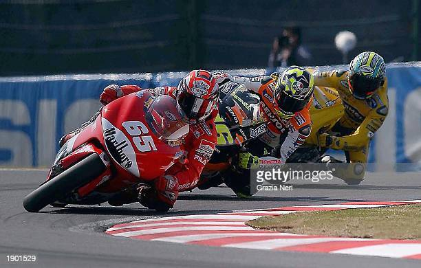 Loris Capirossi of Italy and the Marlboro Ducati team leads Valentino Rossi of Italy and the Repsol Honda team and Max Biaggi of Italy and the Honda...
