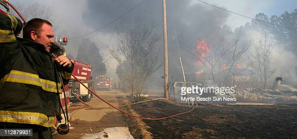 A Loris firefighter adjusts his air pack while he looks toward the ruins of a home in western Horry County on Sunday February 10 2008