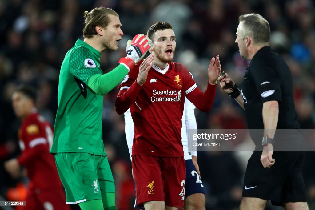 Loris Karius of Liverpool and teammate Andy Robertson of Liverpool confront referee Jonathan Moss during the Premier League match between Liverpool and Tottenham Hotspur at Anfield on February 4, 2018 in Liverpool, England.