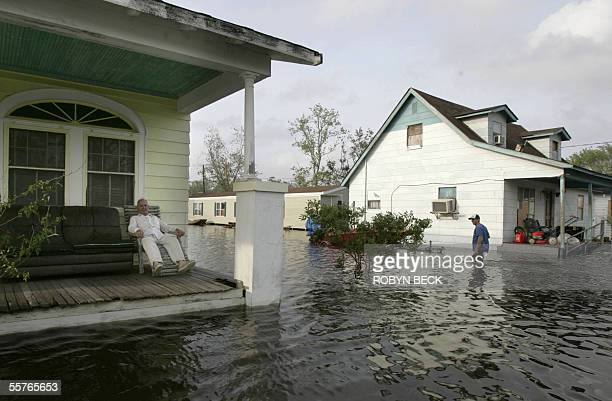 Loris Verdin sits on his porch along Route 45 as a neighbor walks through the flood waters of about three feet in Lafitte some 25 miles south of New...