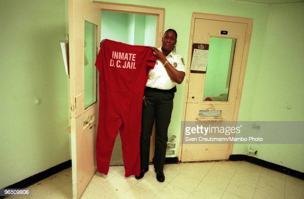 Lorita Burnside Corporal in the Miami Women Detention Center holds up an inmate overall as she stands in front of the cell where Gregory Hemingway...