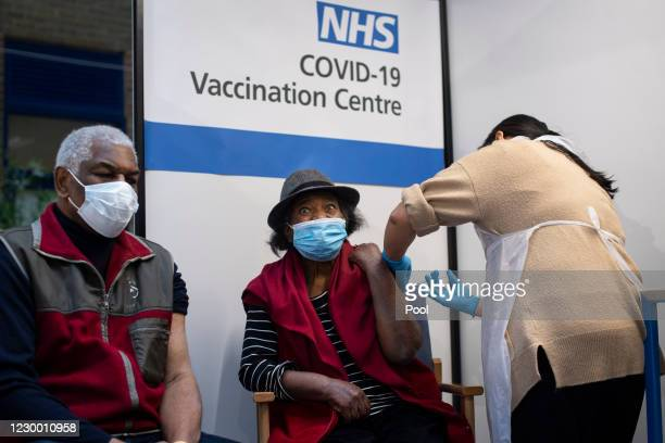 Lorna Lucas reacts as she receives the first of two Pfizer/BioNTech COVID-19 vaccine jabs shortly before her husband, Winston , also has one...