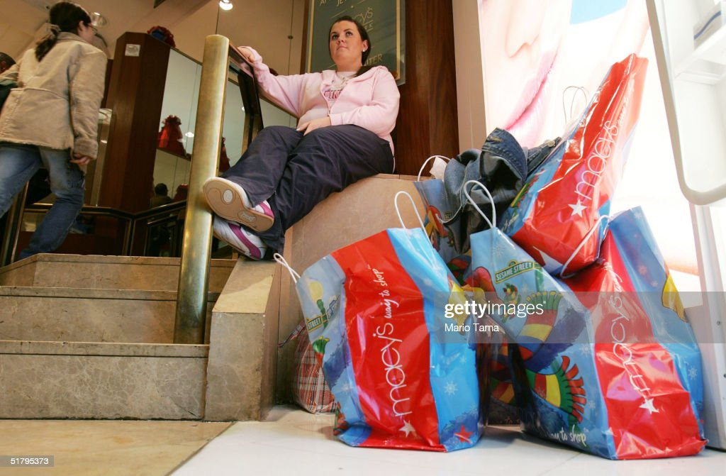 Lorna McCabe from Ireland takes a break from shopping inside Macy's department store November 26, 2004 in New York City. The Friday after Thanksgiving, called 'Black Friday,' is one of the busiest shopping days of the year with stores opening early and a large number of shoppers looking for holiday gifts.