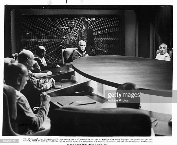 Lorne Greene speaks as Richard Hatch listens from behind him in a scene from the television series 'Battlestar Galactica', 1978.